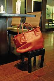 Hanging your purse on a chair in a restaurant Solo Travel Mistakes to Avoid