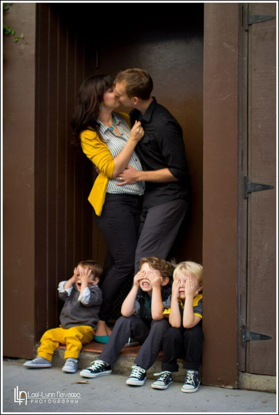Parents kissing children not wtahcing Family Photo Shoot Idea